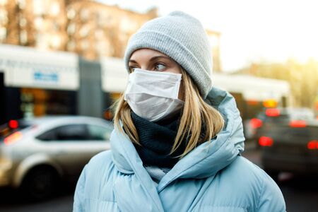 Blonde in mask is standing next to bus for walk on street in city during day.