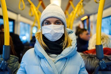 Girl in medical mask standing in bus lounge next to yellow handrails in afternoon.