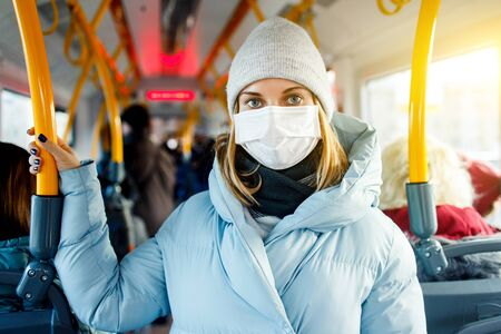 Young woman in medical mask standing in bus lounge next to yellow handrails in afternoon. Banco de Imagens