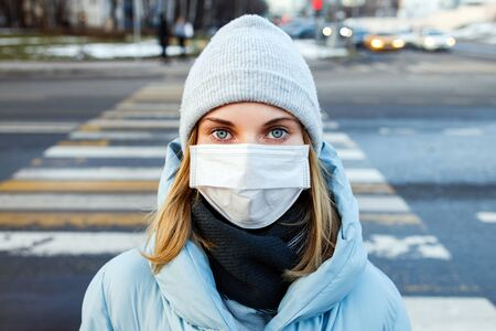 Blonde woman in mask looking at camera on walk on street in city during day. Coronavirus epidemic Banco de Imagens