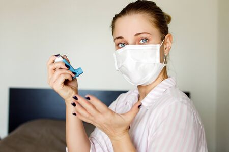 Close-up of sick woman in a medical mask with bronchodilator in her hand . Coronavirus epidemic