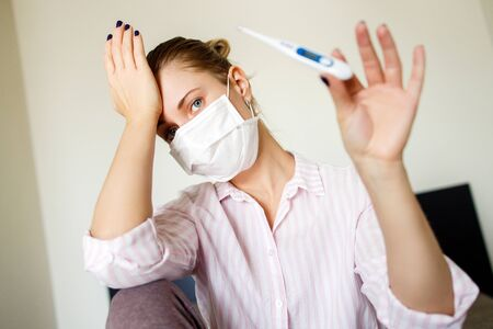Close-up of young female in medical mask with thermometer in her hand . Coronavirus epidemic