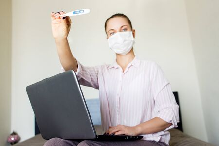 Woman in medical mask looking at camera with thermometer in hand, with laptop. Coronavirus epidemic Banco de Imagens
