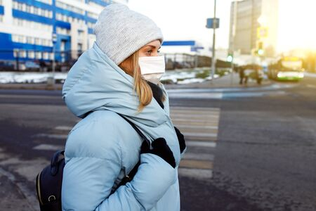 Young woman in mask on walk on street in city during day. Banco de Imagens