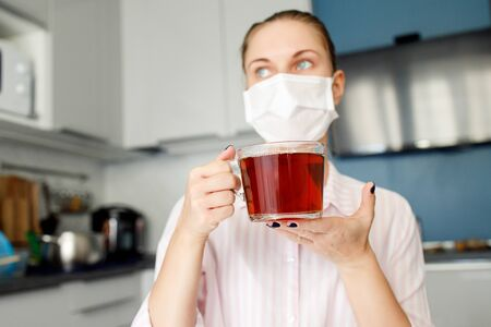 Sick woman in medical mask looking at side with mug of tea in hand standing in kitchen in apartment