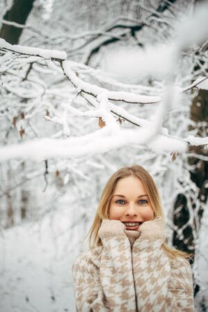 Happy woman with palms near her face on background of snowy trees for walk in winter forest