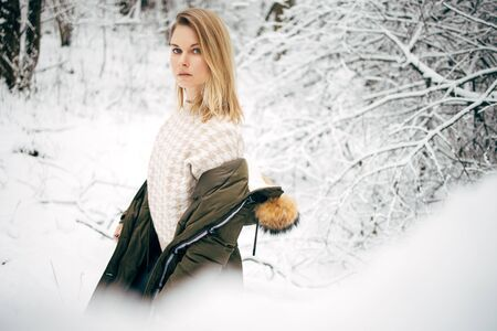Blonde on background of snowy trees for walk in winter forest in afternoon