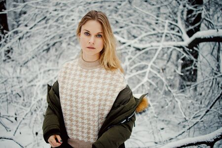 Blonde woman on background of snowy trees for walk in winter forest