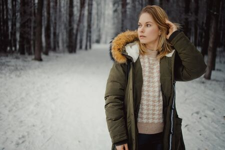 Young woman looks away on background of snowy trees for walk in winter forest Banco de Imagens