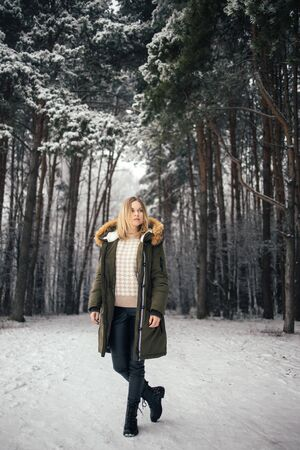 Young woman in full growth on background of snowy trees on walk in winter forest