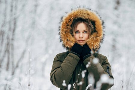 Blonde woman on background of snowy trees on walk in winter forest