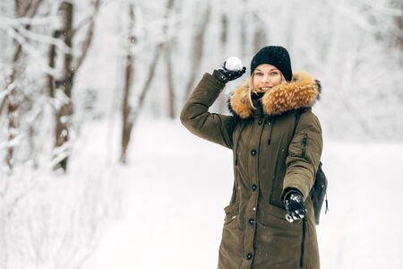Young girl with snow in hands on walk in winter forest Banco de Imagens