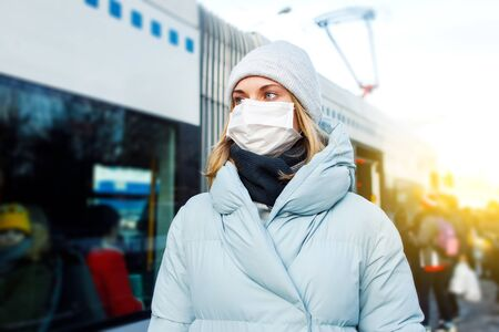 Blonde woman in mask is standing next to bus for walk on street in city during day.