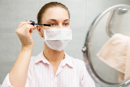 Close-up of young blonde in medical with mascara and mirror in hand