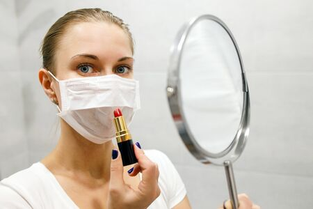 Close-up of young blonde woman in medical mask with lipstick and mirror in her hand