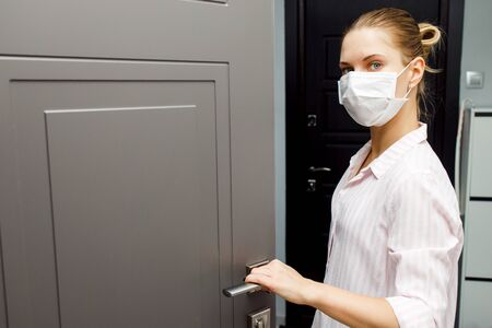 Close-up of young blonde in medical mask opening door