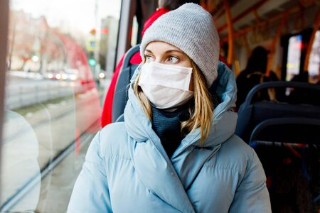 Masked blonde sitting on bus near window during day.
