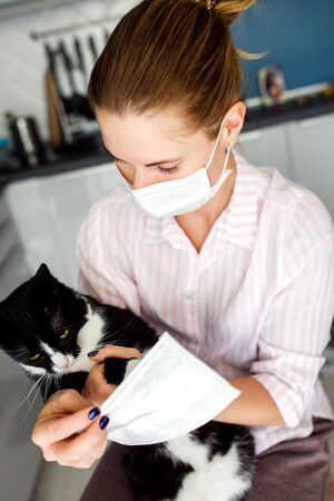 Closeup of young blonde in medical mask cat standing