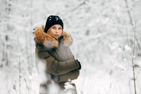 Young girl looking at camera on background of snowy trees on walk in winter forest