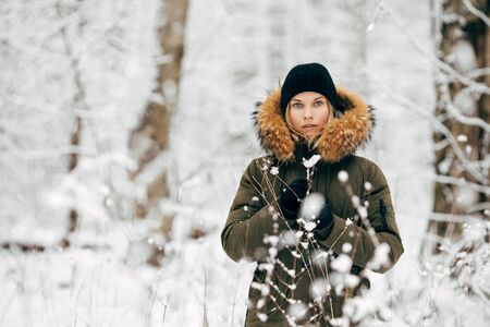 Girl on background of snowy trees on walk in winter forest in afternoon Banco de Imagens