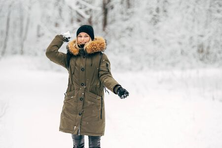 Young woman with snow in hands on walk in winter forest in afternoon Banco de Imagens