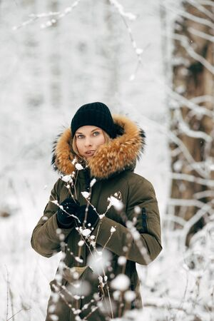 Young girl on background of snowy trees on walk in winter forest