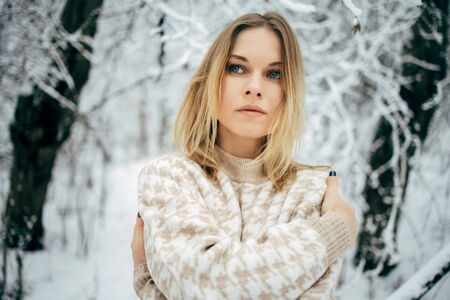 Young woman looking at side on background of snowy trees for walk in winter forest