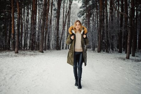 Woman in jacket on background of snowy trees for walk in winter forest