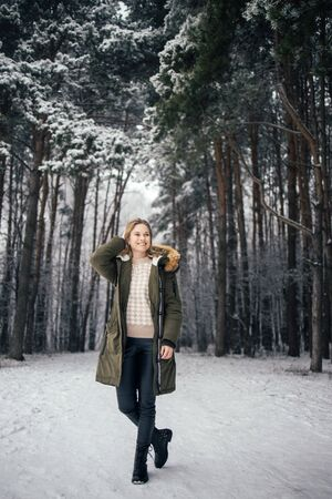 Woman in full growth on background of snowy trees on walk in winter forest Banco de Imagens