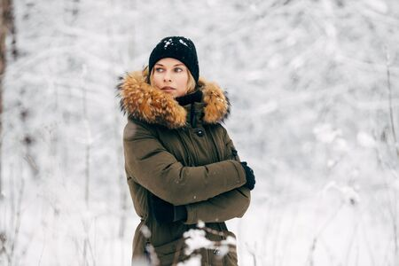 Young girl looking at side on background of snowy trees on walk in winter forest Banco de Imagens