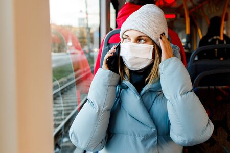 Young masked woman talking on phone while sitting on bus near window during day.