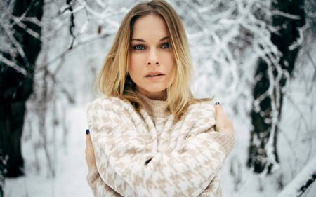 Young woman looking at camera on background of snowy trees for walk in winter forest