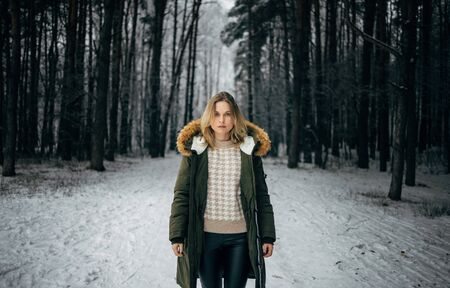 Young woman in jacket on background of snowy trees for walk in winter forest