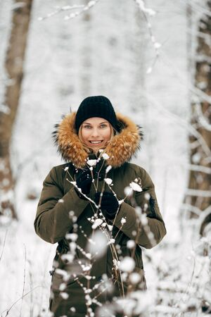 Young woman on background of snowy trees on walk in winter forest