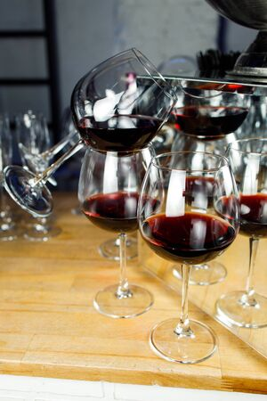 Wine glasses with red wine on wooden table close-up