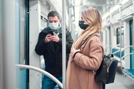 Man with phone in hands and woman in medical masks standing in subway car.