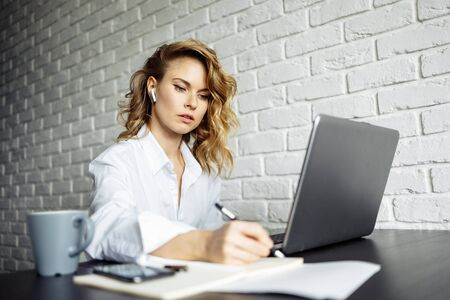 Serious woman with curly hair sitting at table with laptop.