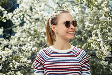 Smiling girl in sunglasses on background of blossoming apple tree