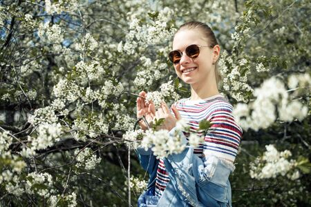 Happy woman in sunglasses on background of blossoming apple tree Foto de archivo
