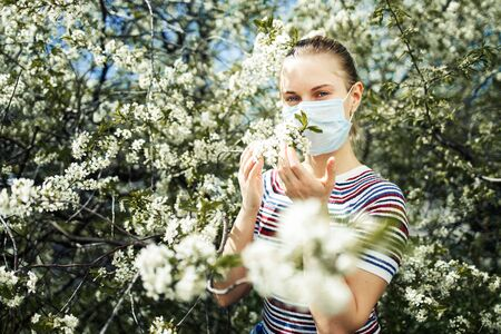 Side view of girl in medical mask on background of blossoming apple tree on summer day. Banco de Imagens