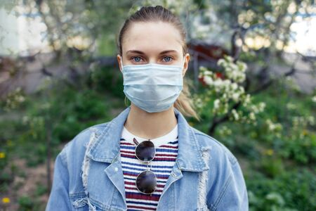 Young girl in medical mask on walk on street