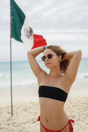 Cheerful woman in swimsuit standing near flag