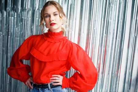 Serious blonde in red sweater on blurry background