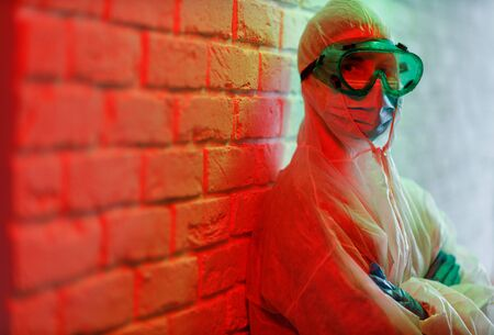 Doctor in protective suit and glasses on background of brick wall in red zone. Coronavirus pandemic