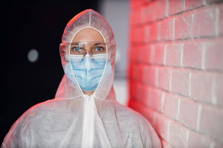 Doctor in protective suit on background of brick wall. Banco de Imagens