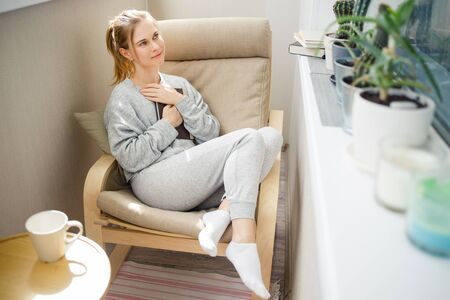 Happy woman with book in her hands sitting on beige armchair in apartment