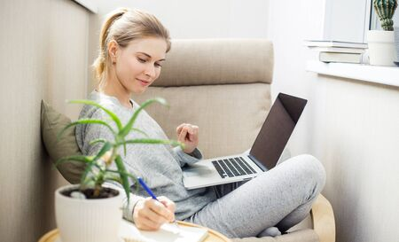 Woman in gray home suit with laptop in her hands sitting in chair on apartment
