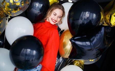 Happy blonde girl in red sweater near balloons Banco de Imagens