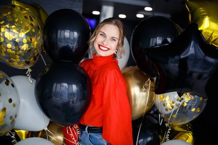 Happy blonde woman in red sweater near balloons Banco de Imagens