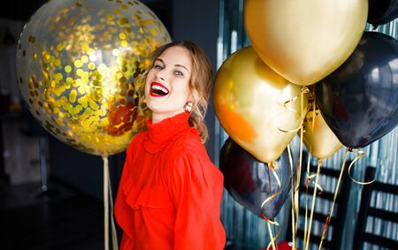Happy woman in red sweater near balloons Banco de Imagens